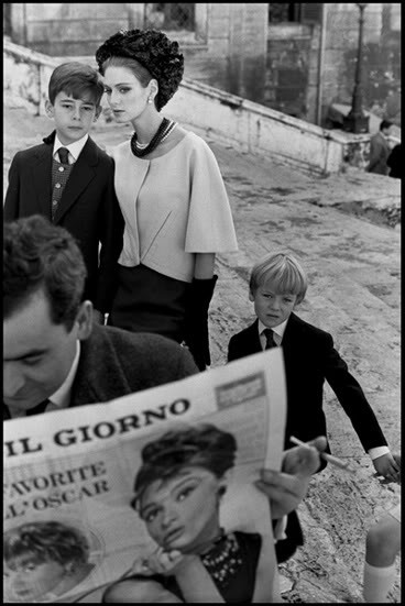 Fashion for Harpers BazaarModel Deborah Dixon, wearing Italian Haute Couture, with children and man reading newspaper, 1962, Rome